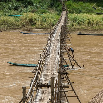Footbridge - Wooden footbridge with a worker busy at its consolidation, in Laos