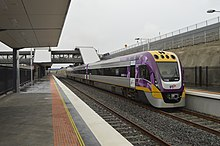 Silver, purple and yellow three-carriage train waiting at a railway station.