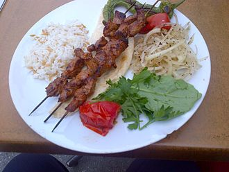 "Shish kebab - Shish kebab with ""şehriyeli pilav"" (orzo pilaf), onions with sumac, a grilled pepper, a slice of tomato (also grilled) and rucula leaves."