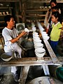 景德镇古窑民俗博览区 一位师傅正在展示半成品的瓷器.jpg