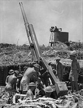 Eight men wearing only shorts and steel helmets attending to a large artillery gun which is positioned in a pit. The six men on the left are working on the gun, and the two men on the right are standing watching them.