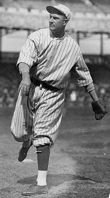 A man in a white baseball uniform with dark pinstripes having just thrown a ball.