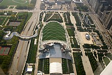 Aerial view of a green park with large roads running vertically at left and right and horizontally at the top. A curving metal bridge crosses the road on the left. Sidewalks divide the park into different areas, and it includes buildings and sculptures.