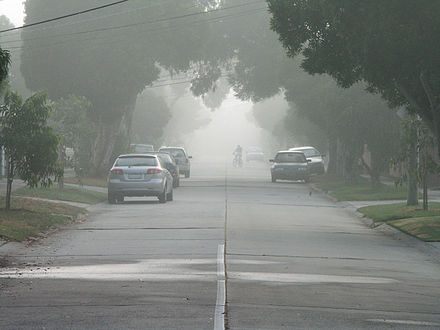 Light fog reduces visibility on a suburban street, rendering the cyclist very hazy at about 200 m (220 yd). The limit of visibility is about 400 m (440 yd), which is before the end of the street. 20080313 Foggy Street.jpg