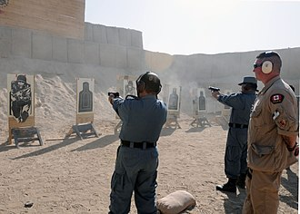 Afghanistan–Canada relations - Constable Lorant Haged, Royal Canadian Mounted Police and instructor at the leadership and management course, observes ANP  as they shot at targets on a 9mm familiarization range Dec. 3. The ANP are attending a six-month Leadership and Management course that will focus on teaching them to run more efficient police sub-stations.