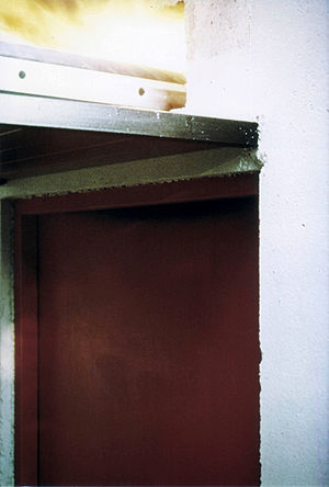 Legal code (municipal) - Building Code Violation: No firestop in the cable tray penetration above the fire door in the fire-resistance rated concrete wall.