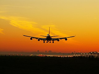 Airplane landing at sunset.