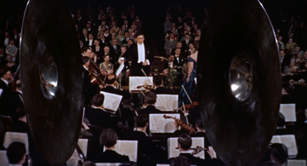 Bernard Herrmann conducting the orchestra in a scene from The Man Who Knew Too Much (1956) Alfred Hitchcock The Man Who Know Too Much 1956 trailer.png