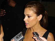 Alyssa Milano speaking into several audio recorders during an interview