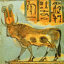 Painting of a bull on a platform. The bull has a yellow disk and a pair of feathers between its horns.