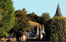 A front-facing view of Bentworth's Primary School with the church spire directly behind
