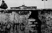 Porción del Muro de Berlín parcialmente destruida vista desde el lado occidental, con un guardia fronterizo y la Puerta de Brandeburgo al fondo, noviembre de 1989