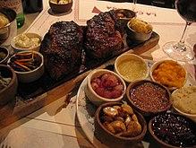 Bord med et kutt av argentinsk biff, vin, sauser og krydder