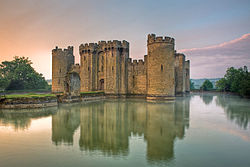 Photo of Bodiam Castle at sunset with towers and battlements reflected in a wide moat. A path leads away from the entrance of the castle across two islands