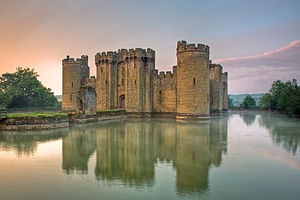 Photo of Bodiam Castle at sunset with towers and battlements reflected in a wide moat. A path leads away from the entrance of the castle across two islands.