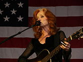 A woman with red hair wearing black clothing and hoop earrings playing the guitar and singing into a microphone. The American flag appears in the background.