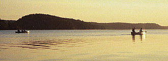 Boundary Waters Canoe Area Wilderness Act - Two canoes paddling into the sunrise on Saganaga Lake.