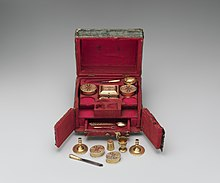A small, elaborate box, featuring a hinged lid, two swing doors at the front and a small pull-out drawer; the interior is entirely red and features small items that seem to be part of a toilette set