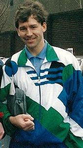 A man in a white, green and blue tracksuit with a small bag under his right arm