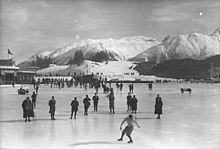 A figure skater performing on a large frozen outdoor area with a group of people nearby on the ice. The background shows snow-covered mountains and a building.