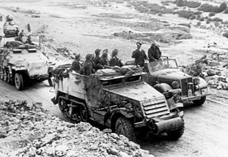 Rommel speaks with troops who are using a captured American M3 half-track, Tunisia. Bundesarchiv Bild 146-1990-071-31, Nordafrika, Rommel, Bayerlein.jpg