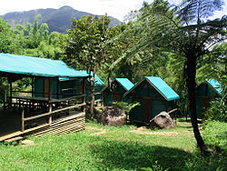 Several bungalows made of wood and blue-green tarp, along with a covered eating area.