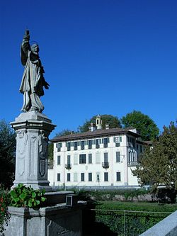 Statue of St. Charles Borromeo and Villa Visconti Maineri.