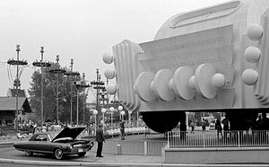 Car with its hood up in front of a World's Fair pavilion