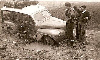 John Crosthwaite - Crosthwaite, standing, examining Mercury. Front wheel in mine hole. Greece 1949