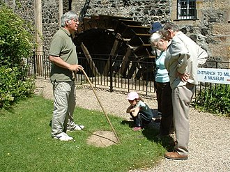 Dalgarven Mill – Museum of Ayrshire Country Life and Costume - A trustee leading a guided tour, at the cup and ring marked stone.