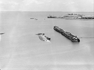 Axis naval activity in Australian waters - A sunken ship and burnt-out wharf in Darwin Harbour following the first Japanese air raid.