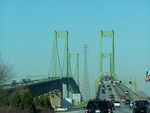 A congested divided freeway approaching a green twin-span bridge