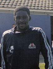 A young man, wearing a black tracksuit top with blue and white stripes along the sleeves. Behind him is a building with a blue wall.