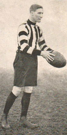A dark-haired footballer in a long-sleeve black-and-white vertically-striped guernsey and black shorts holding a football