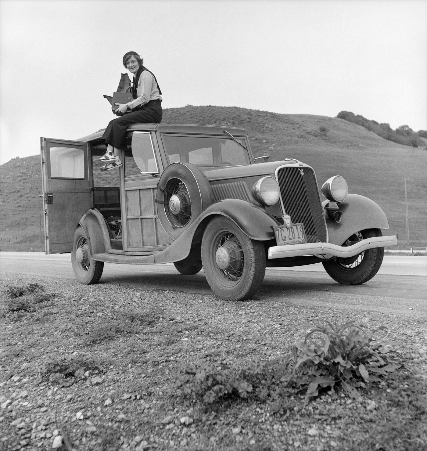 Dorothea Lange atop automobile in California (restored).jpg