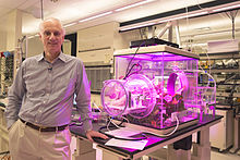 Dr. Lackner next to benchtop greenhouse with prototype air capture unit.jpg