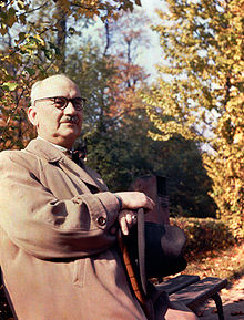 An elderly man, wearing a grey coat and holding a black hat sits in a garden in autumn.