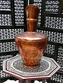 Egyptian embassy display copper vase on inlaid table by carved screen.jpg
