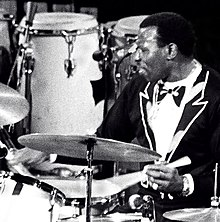 Elvin Jones in a black suit performing behind a drum kit