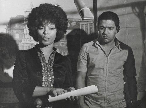 Elza recebendo o diploma de Embaixatriz do Samba no Museu da Imagem e do Som, com Garrincha ao fundo, em 1971.