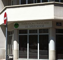 "Windows of a modern-fronted office building on a city street, with a sign above which reads ""Fédération française de spéléologie""."