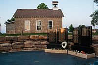 Malý památník černé žuly s jednopokojovým školním domem v pozadí