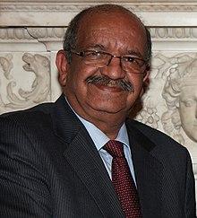 photo d'un homme chauve et moustachu portant des lunettes, un costume et une cravate, en arrière-plan figure une mur avec des bas-reliefs.