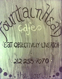 A wooden sign displays the words 'FountainHead Cafe: Eat Objectively, Live Rich'