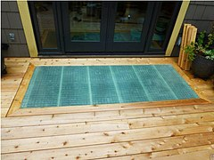 Pine decking with a panel of fiberglass showing a fine grid set in a mitered pine frame. The fiberglass is slightly blue-green, and sits squarely in front of the glass doors to the house.