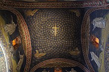Interior image of the relatively small sail vault ceiling at the cross intersection of the Mausoleum of Galla Placidia with intact mosaic decoration of gold stars on a blue background and a gold cross at the center