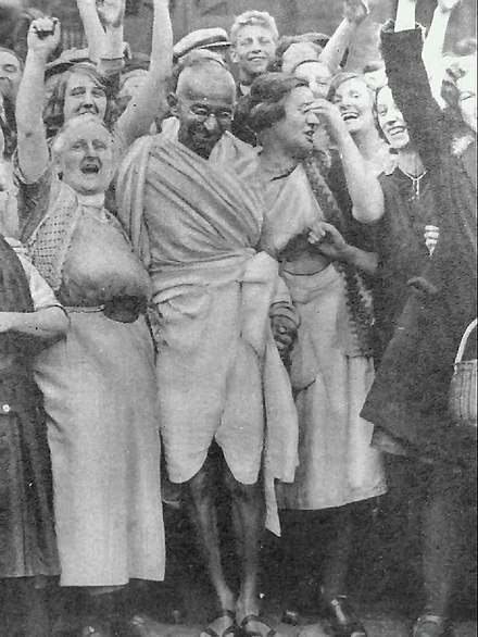 Mohandas Gandhi, here meeting with women textile workers in Britain, was a leadership figure of India's anti-colonial and social democratic Indian National Congress still active today Gandhi at Darwen with women.jpg