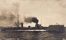 A German Torpedo boat cruising at sea with smoke billowing from a stack amidships.