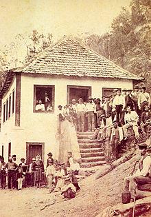 Fotografia que mostra uma multidão de pessoas se reuniram em torno e sobre os degraus de uma casa de estuque branco com um telhado de quadril coberto de telhas de madeira situada em uma encosta íngreme de uma colina arborizada
