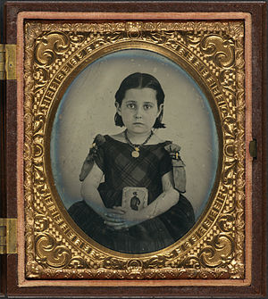 Mourning - Girl in a mourning dress holding a framed photograph of her father, who presumably died during the American Civil War.